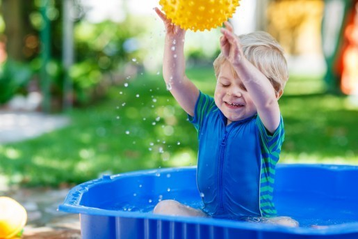 Little Toddler Boy Having Fun With Splashing Water In Summer Gar
